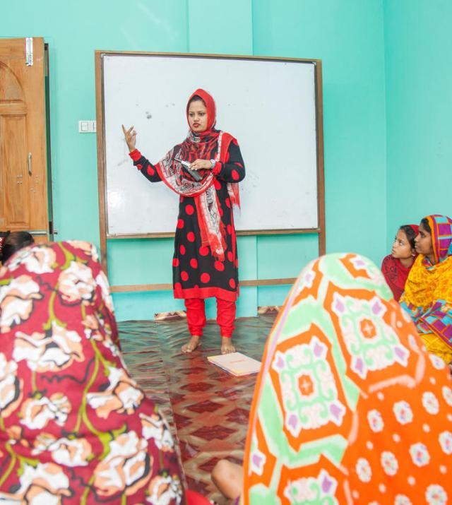 Photo of a woman speaking to a group of women